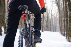Bicicleta da equitação do motociclista da montanha na fuga nevado no inverno bonito Forest Free Space para o texto Imagens de Stock