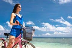 Bicicleta da equitação do turista da mulher na praia nas férias Imagem de Stock