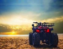 Bicicleta da sujeira de quatro veículos com rodas na areia da praia do mar durante o nascer do sol com o céu colorido dramático imagens de stock