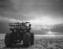 Bicicleta da sujeira de quatro veículos com rodas na areia da praia do mar durante o nascer do sol com o céu colorido dramático,  fotografia de stock