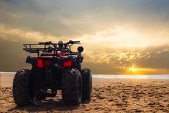 Bicicleta da sujeira de quatro veículos com rodas na areia da praia do mar durante o por do sol fotos de stock royalty free