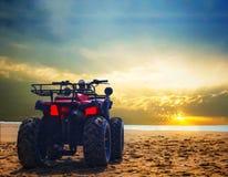 Bicicleta da sujeira de quatro ve?culos com rodas na areia da praia do mar durante o nascer do sol com o c?u colorido dram?tico imagens de stock