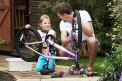 Bicicleta de And Daughter Cleaning do pai junto imagens de stock royalty free