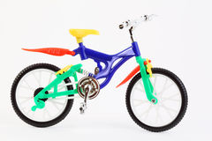 Bicicleta de dos ruedas del juguete plástico en blanco foto de archivo