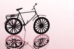 Bicicleta de encontro ao fundo vermelho claro Fotos de Stock Royalty Free