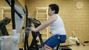 Bicicleta de exercício gorda do exercício do rapaz pequeno na sala da aptidão Estilo de vida saudável do conceito video estoque