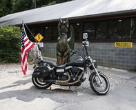Bicicleta de Harley Davidson na frente da cauda da estátua do dragão foto de stock