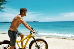 Bicicleta de la arena del montar a caballo del hombre en la playa Actividad del deporte del verano Imagen de archivo