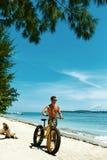 Bicicleta de la arena del montar a caballo del hombre en la playa Actividad del deporte del verano Fotografía de archivo