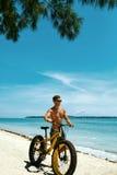 Bicicleta de la arena del montar a caballo del hombre en la playa Actividad del deporte del verano Foto de archivo libre de regalías