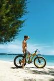 Bicicleta de la arena del montar a caballo del hombre en la playa Actividad del deporte del verano Imagen de archivo libre de regalías