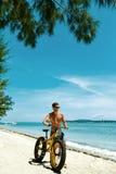 Bicicleta de la arena del montar a caballo del hombre en la playa Actividad del deporte del verano Fotografía de archivo libre de regalías