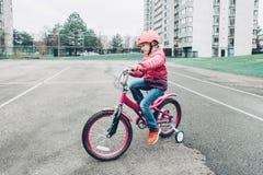 Bicicleta de la bici del rosa del montar a caballo de la muchacha del preescolar en casco en el camino del patio trasero afuera e fotografía de archivo