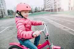 Bicicleta de la bici del rosa del montar a caballo de la muchacha del preescolar en casco en el camino del patio trasero afuera e fotografía de archivo libre de regalías