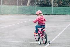 Bicicleta de la bici del rosa del montar a caballo de la muchacha del preescolar en casco en el camino del patio trasero afuera e imágenes de archivo libres de regalías