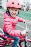 Bicicleta de la bici del rosa del montar a caballo de la muchacha del preescolar en casco en el camino del patio trasero afuera e imagen de archivo