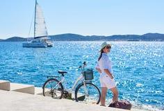 Bicicleta de la ciudad del montar a caballo de la mujer joven cerca del mar imágenes de archivo libres de regalías