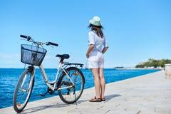 Bicicleta de la ciudad del montar a caballo de la mujer joven cerca del mar imagenes de archivo