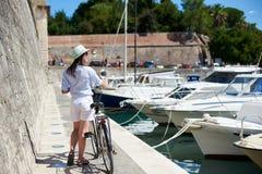 Bicicleta de la ciudad del montar a caballo de la mujer joven cerca del mar imagen de archivo libre de regalías