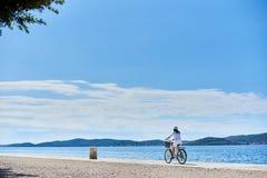 Bicicleta de la ciudad del montar a caballo de la mujer joven cerca del mar fotografía de archivo