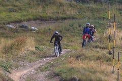 Bicicleta de la montaña del montar a caballo del hombre cuesta abajo y dos amigos que lo miran imágenes de archivo libres de regalías