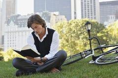 Bicicleta de Reading Book By del hombre de negocios en parque Fotografía de archivo