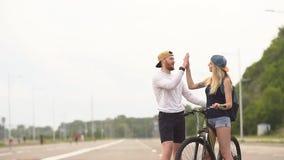 Bicicleta de risa sonriente del montar a caballo de los pares jovenes felices, cámara lenta metrajes