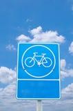Bicicleta de Roadsign bajo el cielo nublado Foto de archivo