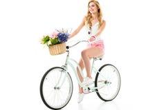 Bicicleta de sorriso nova da equitação da menina com as flores na cesta Imagem de Stock Royalty Free