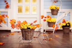 Bicicleta decorativa con la cesta con las hojas y el otoño GR del amarillo Imagen de archivo