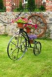 Bicicleta decorativa del metal con las flores Fotos de archivo libres de regalías