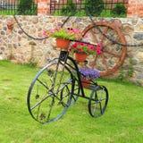 Bicicleta decorativa del metal con las flores Foto de archivo libre de regalías