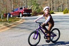 Bicicleta del montar a caballo de la chica joven Imágenes de archivo libres de regalías