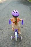 Bicicleta del montar a caballo de la muchacha con las ruedas de entrenamiento fotos de archivo libres de regalías
