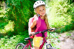 Bicicleta del montar a caballo de la muchacha de los niños al aire libre en bosque Imágenes de archivo libres de regalías