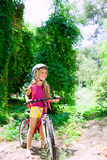 Bicicleta del montar a caballo de la muchacha de los niños al aire libre en bosque Foto de archivo