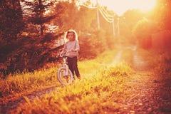 Bicicleta del montar a caballo de la muchacha del niño en la carretera nacional del verano Foto de archivo