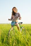 Bicicleta del montar a caballo de la muchacha en campo Fotografía de archivo