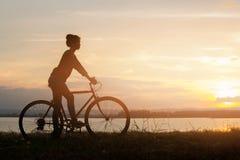 Bicicleta del montar a caballo de la muchacha en el fondo de la puesta del sol o de la salida del sol Fotografía de archivo libre de regalías