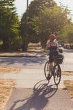 Bicicleta del montar a caballo de la muchacha en puesta del sol imagenes de archivo