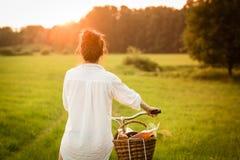 Bicicleta del montar a caballo de la mujer con la cesta de comida fresca Fotografía de archivo libre de regalías