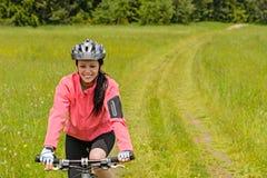 Bicicleta del montar a caballo de la mujer en la trayectoria del prado Imagen de archivo libre de regalías