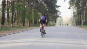 Bicicleta del montar a caballo de Triathlete en parque de la ciudad fuera de la silla de montar Concepto del Triathlon almacen de metraje de vídeo