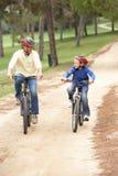 Bicicleta del montar a caballo del abuelo y del nieto en parque Imágenes de archivo libres de regalías