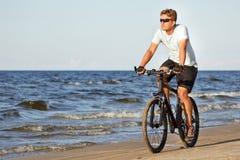 Bicicleta del montar a caballo del hombre en playa Imagenes de archivo