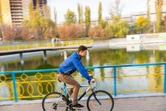 Bicicleta del montar a caballo del hombre joven cerca del agua en otoño Imagen de archivo