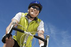 Bicicleta del montar a caballo del hombre mayor contra el cielo Imagen de archivo