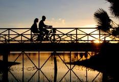 Bicicleta del montar a caballo del motorista en el puente Imágenes de archivo libres de regalías