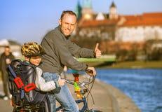 Bicicleta del montar a caballo del padre y del hijo a lo largo de la costa del río Foto de archivo libre de regalías
