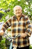 Bicicleta del montar a caballo del viejo hombre Imágenes de archivo libres de regalías
